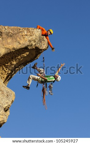 Climbing team struggle to the summit of a challenging rock mountain.