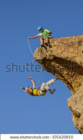 Climbing team struggles on the summit of a challenging rock mountain.