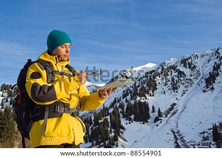 Climbing young adult with map and compass. Aerial view of mountain and blue sky
