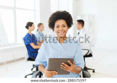 clinic, profession, people and medicine concept - happy african american female doctor or nurse with tablet pc computer over group of medics meeting at hospital
