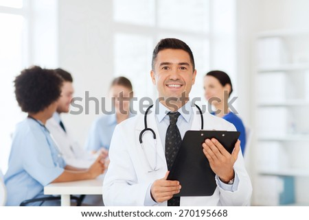 clinic, profession, people and medicine concept - happy male doctor with clipboard over group of medics meeting at hospital