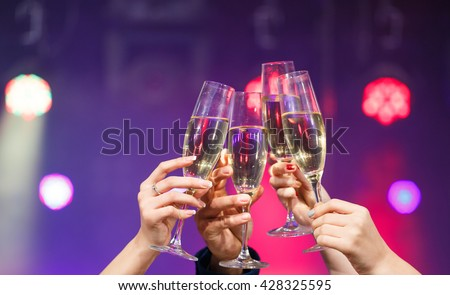 Clinking glasses of champagne in hands on bright lights background #428325595