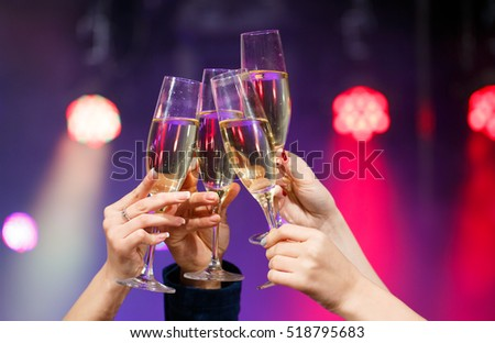 Shutterstock Clinking glasses of champagne in hands on bright lights background