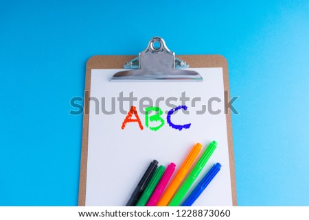 Clipboard and words ABC on blue background with selective focus and crop fragment