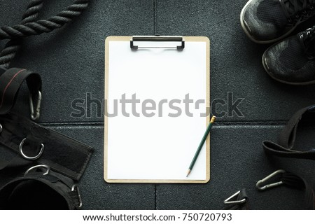 Clipboard check list in Gym with fitness sport equipment background