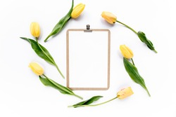 Clipboard mock up with beautiful yellow tulips isolated on white background. Flat lay, top view. Minimalistic office desk. Beauty blog concept.