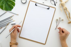 Clipboard mockup, girl draws a pencil drawing, creative artist drawing a4, dandelion,wooden mannequin drawing model top view, flat lay