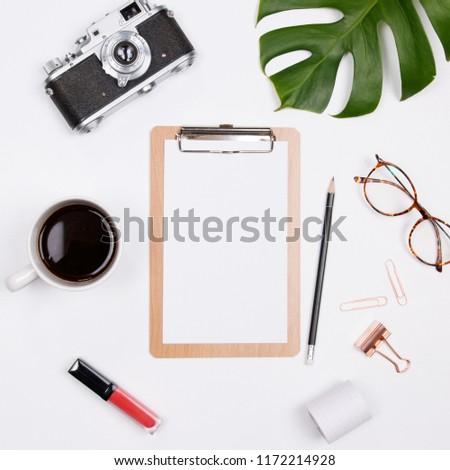 Clipboard mockup with tropical palm leaf, vintage camera, glasses and coffee cup on white background. Flat lay, top view woman blog mockup. summer travel concept.