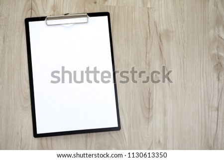 Clipboard with a blank sheet of paper on wooden table background.