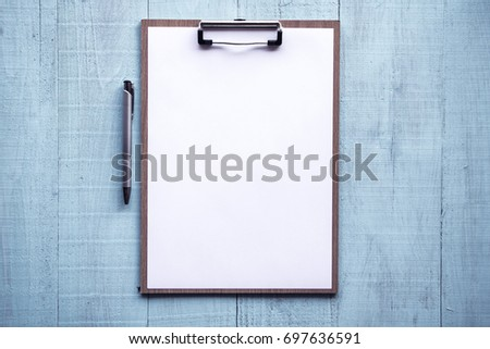 Clipboard with white sheet and pencil on wood background. Top view.Vintage style.blue sky pastel colored