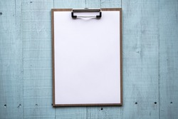 Clipboard with white sheet on wood background. Top view. mock up for word.