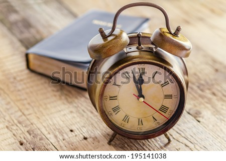Clock and Bible on wood. Concept of clock showing a few minutes to twelve o\'clock. Focus on the clock.