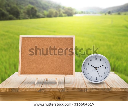 clock and cork board on wood table top with blur green rice fields background
