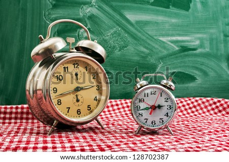 Clock at the kitchen table with red and white checkered tablecloth.