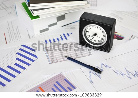 Clock, books and pen on a market report