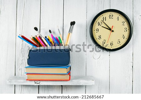 Clock, books and school tools on a wooden shelf. On a white, wooden background.