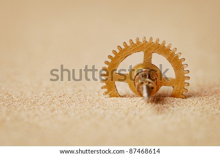 Clock detail - a gear in the sand close up