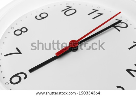 Clock face showing time running to six on white background