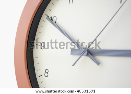 Clock face, taken at an angle.  Cream face, black lettering, sans serif typeface.  Grey hands.  Terracotta circular frame.  White background.