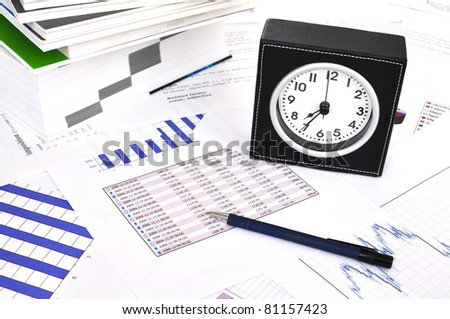 Clock, files and pen on a market report
