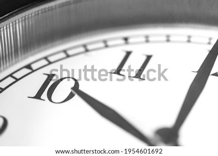 Clock hand pointing ten o'clock on white clock face of Twin bell classic alarm clock
