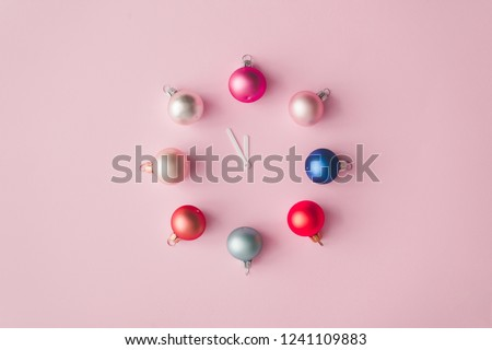 Clock hands with colorful pastel decoration balls on pink painted wall. Minimal time concept. Chrismas eve or new year idea.