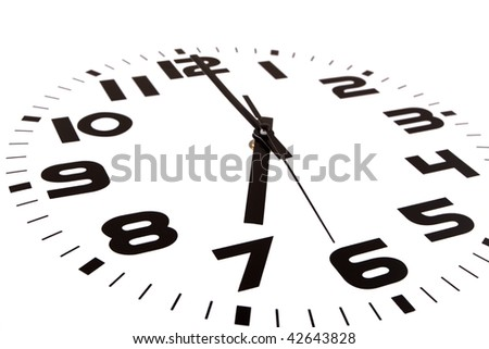 Clock isolated on white marking the seven o'clock hour. The main focus is in the hour hand.