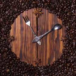 Clock made of coffee, teaspoon, dessert fork and anise on dark wooden background