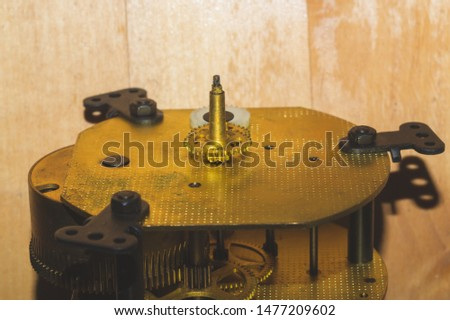 Clock mechanism on wooden table. detail of gears of a mechanical watch