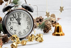 Clock on a light background marking twelve o'clock at night ,surrounded by pineapples, orange bell and a golden garland of gifts.