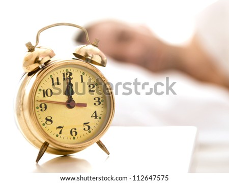 Clock on a table close up, man sleeping in the back