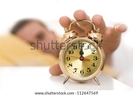 Clock on a table close up, man waking up