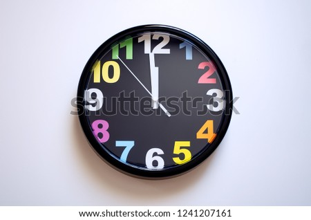 Clock on a white background. A few seconds to midnight. Multi-colored numbers on the clock. #1241207161