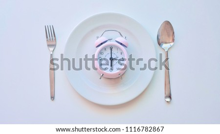 clock on an empty plate, white background. the concept of limiting the intake of food. #1116782867