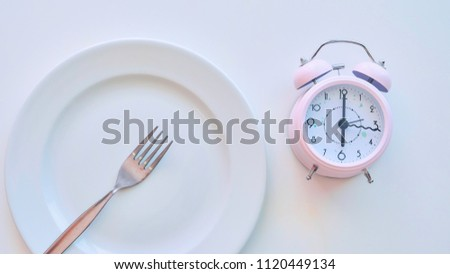 clock on an empty plate, white background. the concept of limiting the intake of food. #1120449134