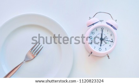 clock on an empty plate, white background. the concept of limiting the intake of food. #1120823324