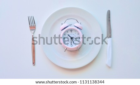 clock on an empty plate, white background. the concept of limiting the intake of food. #1131138344