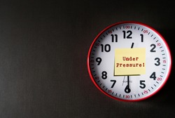 Clock on dark gray copy space background with note written UNDER PRESSURE! means dealing with time constraints which are often outside of control - difficulty task or having insufficient knowledge