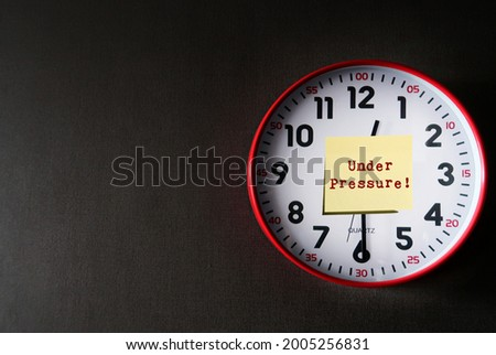 Clock on dark gray copy space background with note written UNDER PRESSURE! means dealing with time constraints which are often outside of control - difficulty task or having insufficient knowledge Stock photo ©