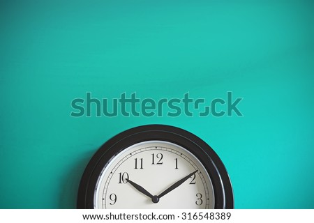 Clock on mint green wall background. Vintage effect. Concept of Time.