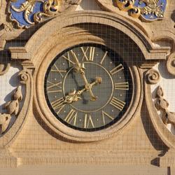 Clock on Palais Stutterheim, Erlangen, Germany. Golden fingers and numbers on grey clock face. Time on clock: 07h56