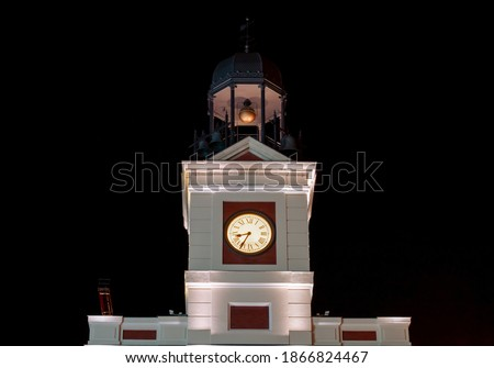 Clock on the tower of the main building in Puerta del Sol square. Clock with its hands illuminated at night in the palace of the post office, current presidency of the Community of Madrid, Spain. Foto stock ©