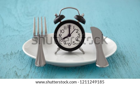 Clock on white plate with fork and knife, intermittent fasting, meal plan, weight loss concept on blue table #1211249185