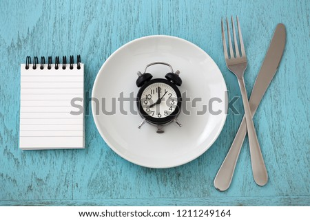 Clock on white plate with fork, knife and notepad, intermittent fasting and weight loss plan concept #1211249164