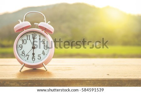 Clock on wood in the morning, blurred nature background. #584591539