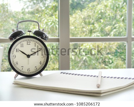 Clock placed beside notebook and pencil on white background. The window beside the desk helps to make the atmosphere better. #1085206172