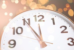 Clock showing five minutes till midnight with bokeh effect, closeup. New Year countdown