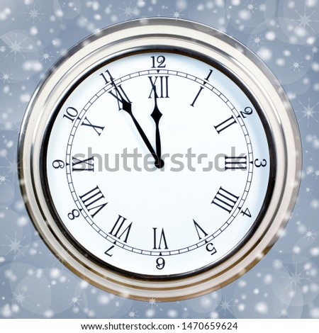 Clock showing five minutes to midnight on background with snowflakes