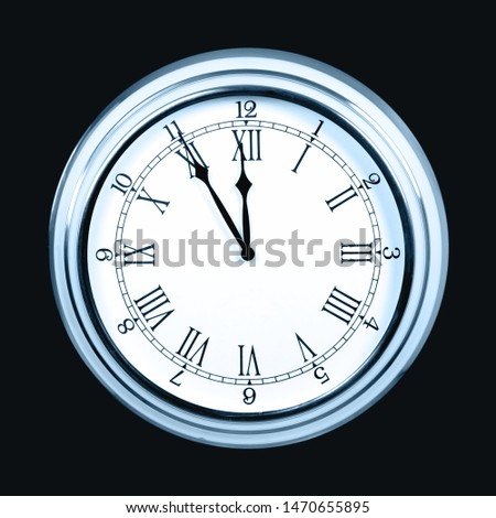 Clock showing five minutes to midnight on dark background