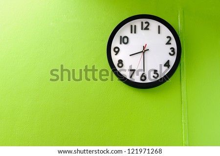 Clock showing 8:30 o'clock on a green wall